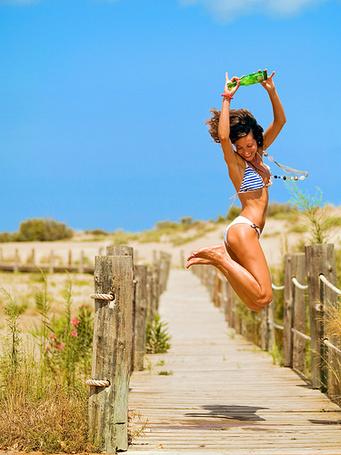 Фото Девушка в купальнике подпрыгнула в воздухе, держа в руках зеленую бутылку