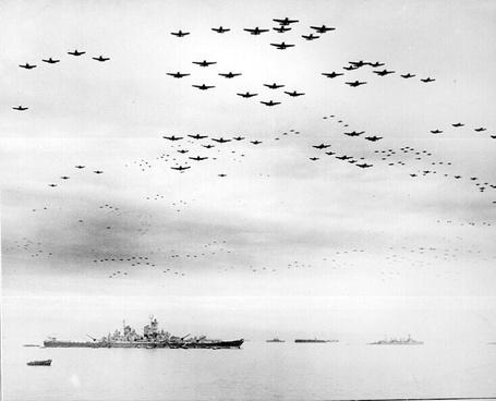 Фото Очень много военных самолетов летят в небе над морем, по которому плывет корабль