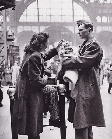 Фото Солдат держит своего малыша на руках на вокзале, и смотрит на свою жену которая поправляет шапочку ребенку, фотограф Alfred Eisenstaedt