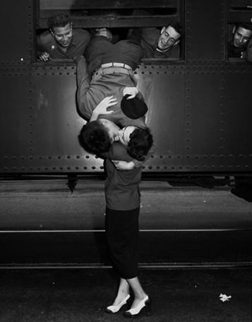 Фото Мужчина целует женщину из окна поезда, его за ноги держат товарищи
