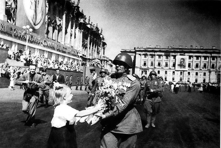 Фото Девочка дарит цветы Герою Советского Союза гвардии полковнику А. Г. Афанасьеву во время парада на Дворцовой площади Ленинграда