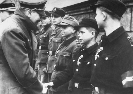 Фото Адольф Гитлер в саду имперской канцелярии награждает юных членов Гитлерюгенд. В центре, награжденные железными крестами 2-го класса, юные уроженцы Силезии: второй справа – 12-летний Альфред Чех / Alfred Czech