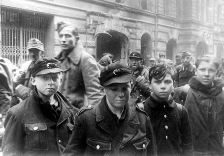 Фото Колонна пленных на улице Берлина / Berlin. На переднем плане «последняя надежда Германии» мальчишки из гитлерюгенда / Hitlerjugend и фольксштурма / Volkssturm, май 1945 года