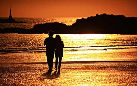 Фото Девушка с мужчиной идут по пляжу на закате