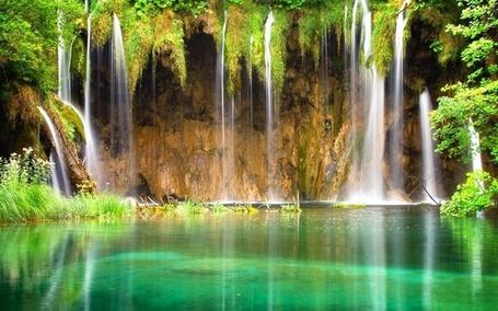 Фото Река в которую течет вода сверху горы, вокруг растут деревья