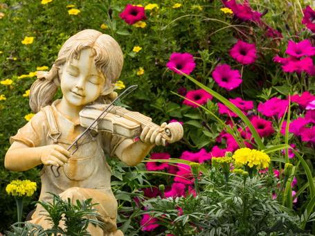 Фото Стоящая в парке, в окружении красивых цветов, гипсовая статуя девочки, играющая на скрипке