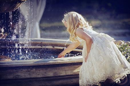 Фото Девочка в белом платьице согнулась к фонтану и тянется ручкой к воде