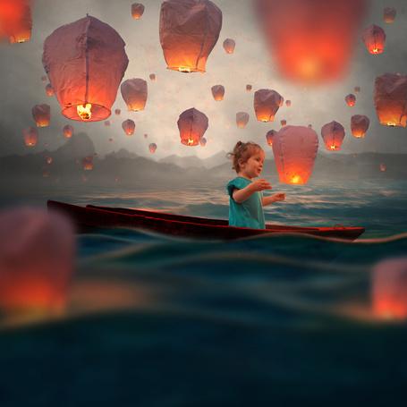Фото Милая девочка в зеленом платье, сидящая в лодке и плывущая по прибрежной морской воде, смотрит на взлетающие китайские фонарики, фотография Garas lonut