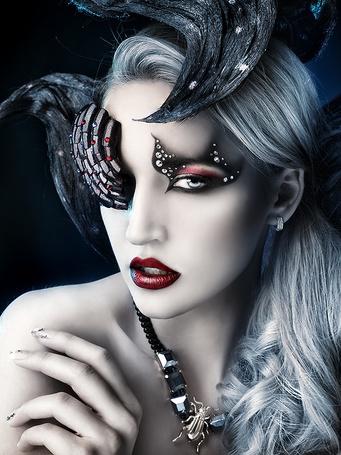 Фото Девушка с ярким макияжем со стразами на лице и колье с жуком на шее