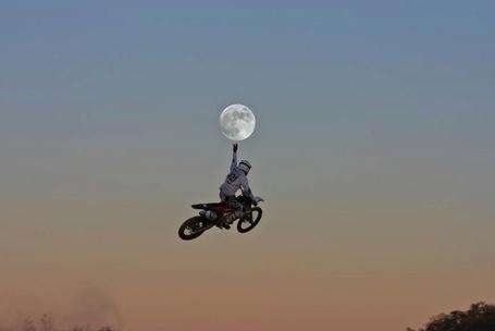 Фото Мотоциклист в прыжке на фоне неба рукой трогает луну