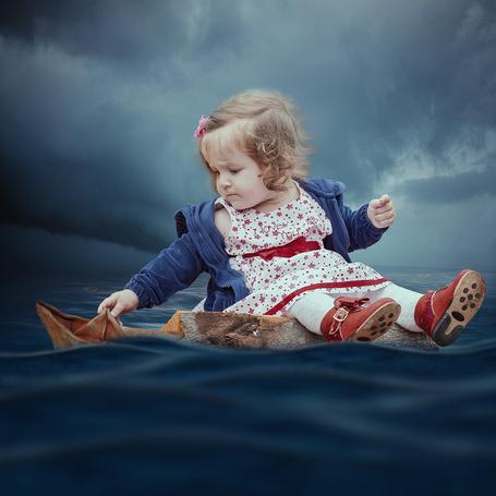 Фото Милая девочка, сидящая на деревянном полене, плывущим по воде, спускает на воду бумажный кораблик на фоне пасмурного неба, фотография Caras lonut