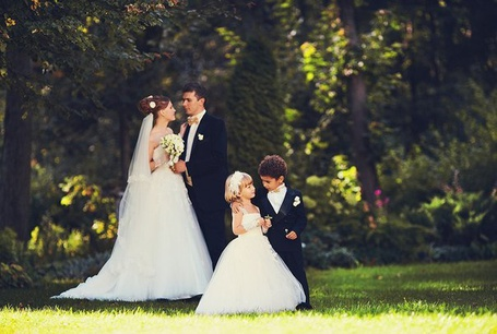 Фото Жених с невестой стоят и нежно смотрят друг на друга, рядом стоят дети, которые повторяют за ними, фотограф Алексей Сычев / Alexey Sychev