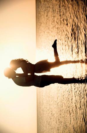 Фото Парень и девушка целуются, стоя в море, в лучах солнца