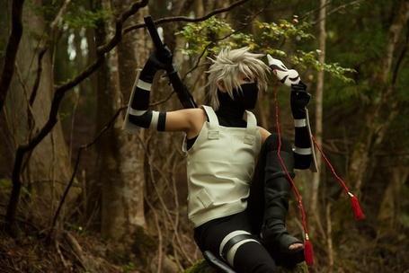 Фото Косплей Какаши / Kakashi анбу сидит на скале в красивом лесу и держит в одной руке катану в другой маску по аниме Наруто / Naruto