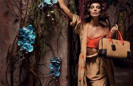 Фото Девушка в коричневом плаще и сумкой у стены с голубыми орхидеями