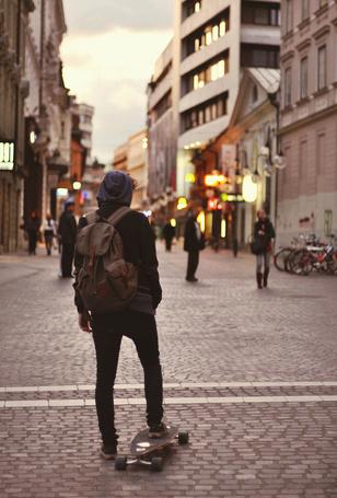 Фото Мужчина, стоя одной ногой на скейтборде, смотрит на людей идущих по улице