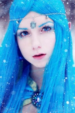 Фото Девушка-эльфийка с голубыми волосами и кулон на голове стоит под снегопадом