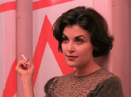 Фото Актриса Sherilyn Fenn / Шерилин Фенн стоит у стены с сигаретой в руках и улыбается, кадр из сериала Twin Peaks / Твин Пикс