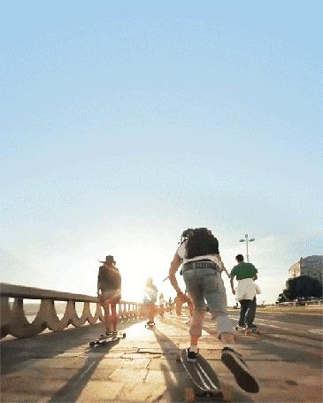 Фото Мужчины едут по дороге на скейтбордах