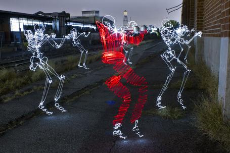 Фото Белые и красный световые скелеты, находящиеся у кирпичной стены здания, расположенного напротив железнодорожного депо, фотография Даррена Пирсона / Darren Pearson