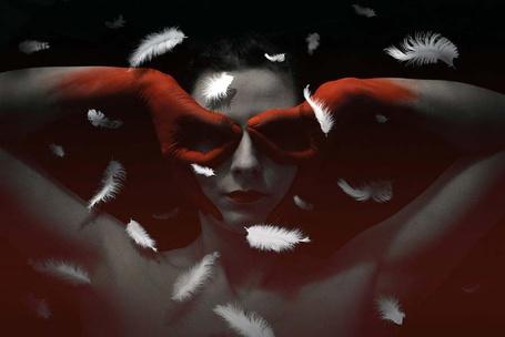 Фото Девушка с раскрашенными в красный цвет руками в виде перчаток, держит руки у глаз, вокруг летают перья, сюрреалистические работа фотохудожницы Валерии Беловой / Valeriya Belova
