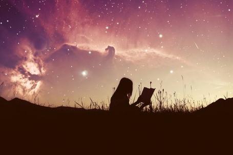 Фото Силуэт девушки, сидящей в траве с книгой в руках, на фоне вечернего закатного неба, в котором проглядывает космос