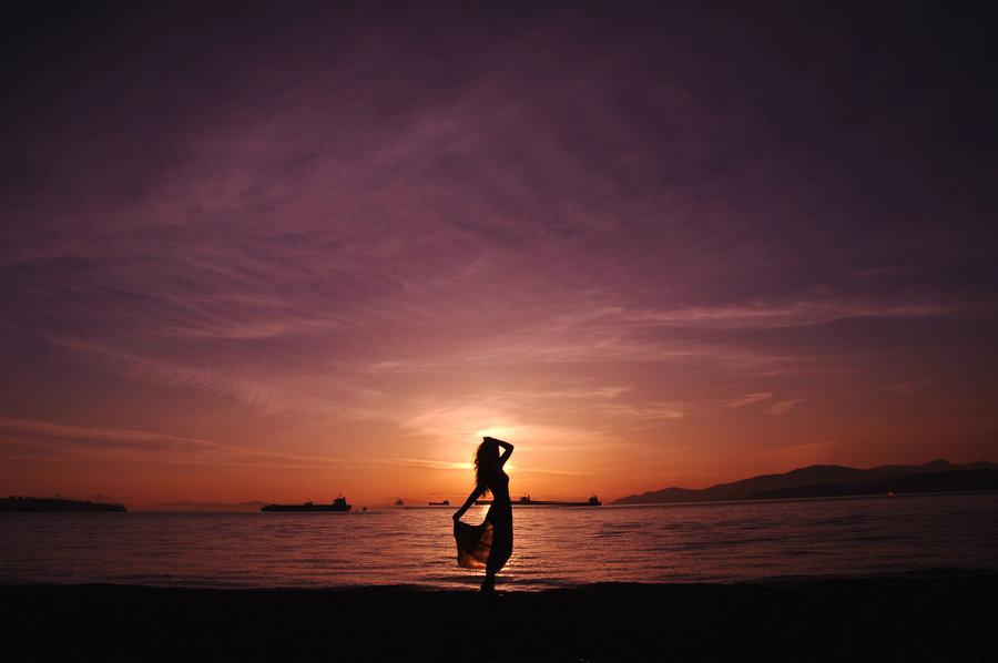 Силуэт девушки, стоящий на берегу моря на фоне заката, автор michellis