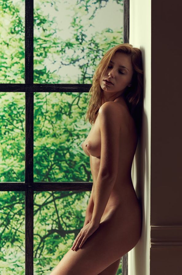 обнаженная девушка стоит за окном
