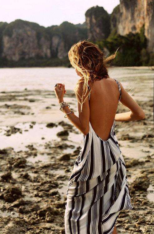 Фото Девушка в белом платье с черными полосками гуляет по берегу моря