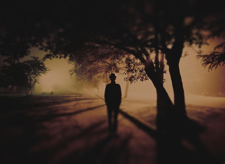 Фото мужчина уходящий по аллее в