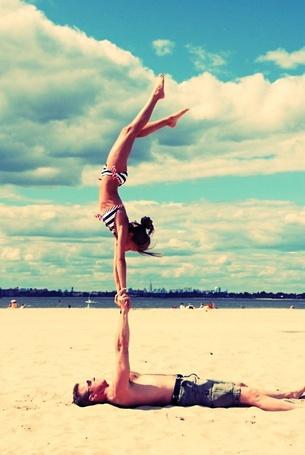 Фото Мужчина поднял девушку над собой, держа руками, на фоне берега озера