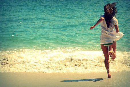 Фото Девушка в майке бежит по пляжу к морю