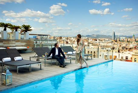 Фото Мужчина и женщина в вечерних нарядах у бассейна отеля Grand Hotel Central 4 с видом на Барселону, Испания / Barcelona / Spain