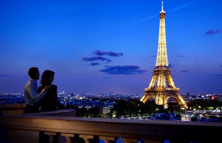 Фото Мужчина и женщина, обнявшись, любуются видом горящей вечерними огнями Эйфелевой башни / Eiffel Tower, Париж, Франция / Paris, France