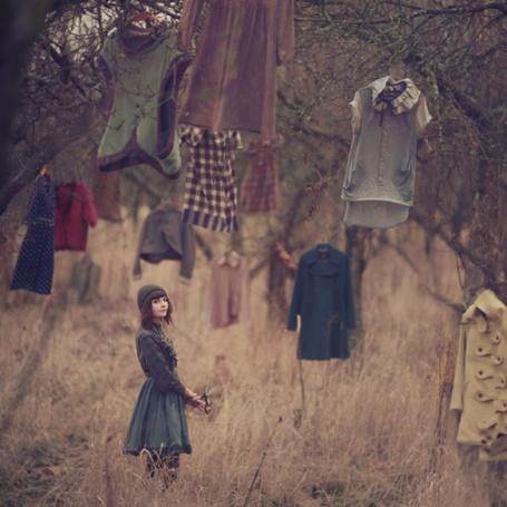 Фото Девушка, которая идет среди деревьев, на которых висит одежда