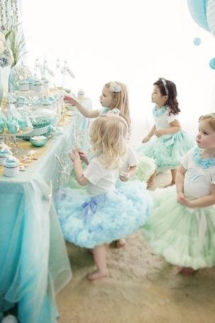 Фото Четыре маленькие девочки в нарядных платьях стоят у праздничного стола