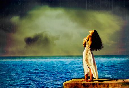 Фото Девушка в белом платье с оголенной спиной стоит на пирсе по дождем, запрокинув голову назад