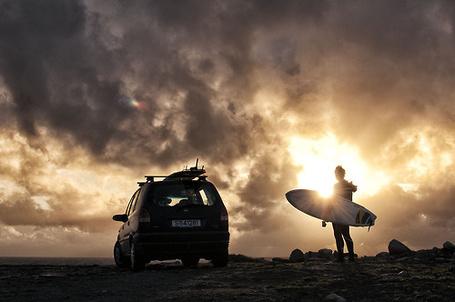 Фото Мужчина с доской для серфинга, идет к машине на фоне неба и облаков