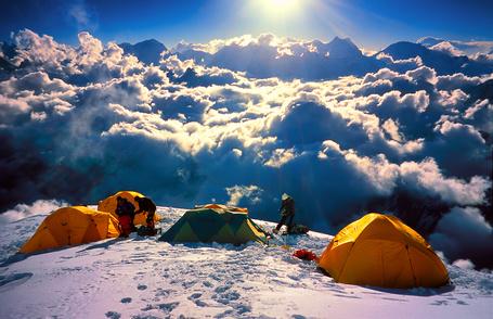Фото Альпинисты с палатками на вершине заснеженной горы, поднимающейся над облаками