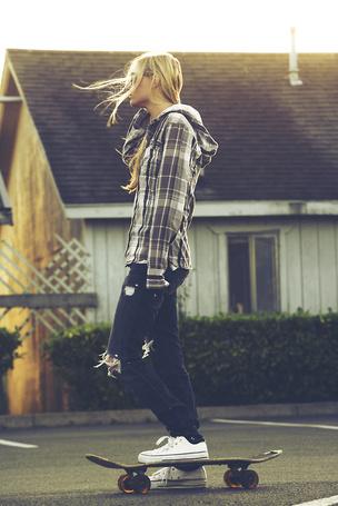 Фото Девушка катается на скейтборде на фоне дома