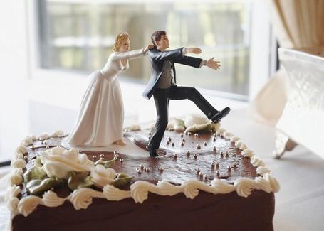 Фото Свадебный торт, на верху которого невеста держит жениха, чтобы он не сбежал