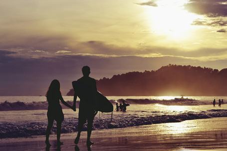 Фото Мужчина несет в руках доску для серфинга, держась другой с девушкой за руку, идя по берегу моря