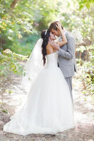 Фото Мужчина и девушка в свадебном платье, стоят на лесной дороге