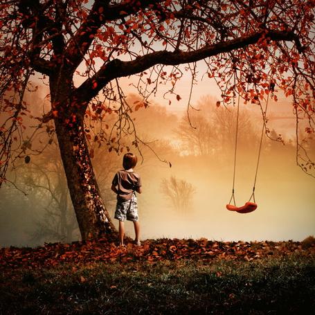Фото Мальчик стоит у дерева, на котором подвешены качели, вокруг клубится дым, фотограф Dragan Todorovic / Драган Тодорович