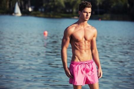 Фото Мужчина со спортивной фигурой в розовых шортах, стоит у воды