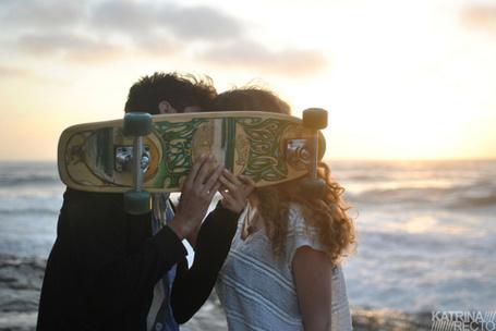 Фото Мужчина и девушка целуются на берегу моря, прикрывшись доской скейтборда, автор Katrina Recto / Катрина Ректо