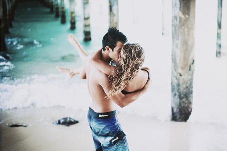 Фото Мужчина целует девушку, держа ее на руках, на берегу моря