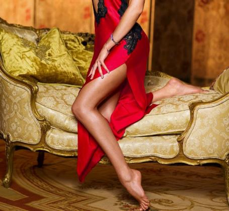 Фото Девушка в красном поставила одну ножку на пальчики на полу, другая лежит на диване