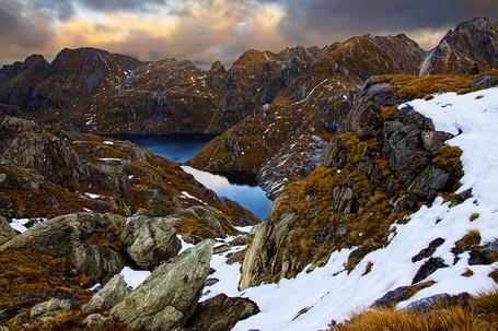 Фото Небольшие озера, находящиеся среди горных образований, покрытых местами снегом на фоне пасмурного неба, фотография Sam