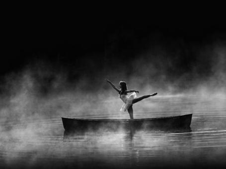 Фото Балерина танцует в лодке, плывущей по туманной реке